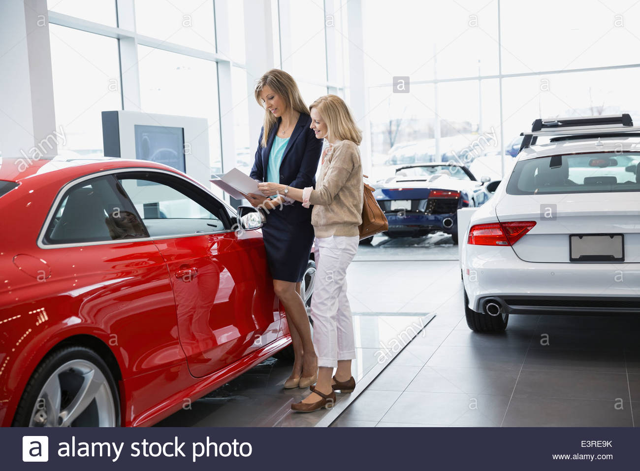 Saleswoman showing woman brochure in car dealership showroom - Stock Image