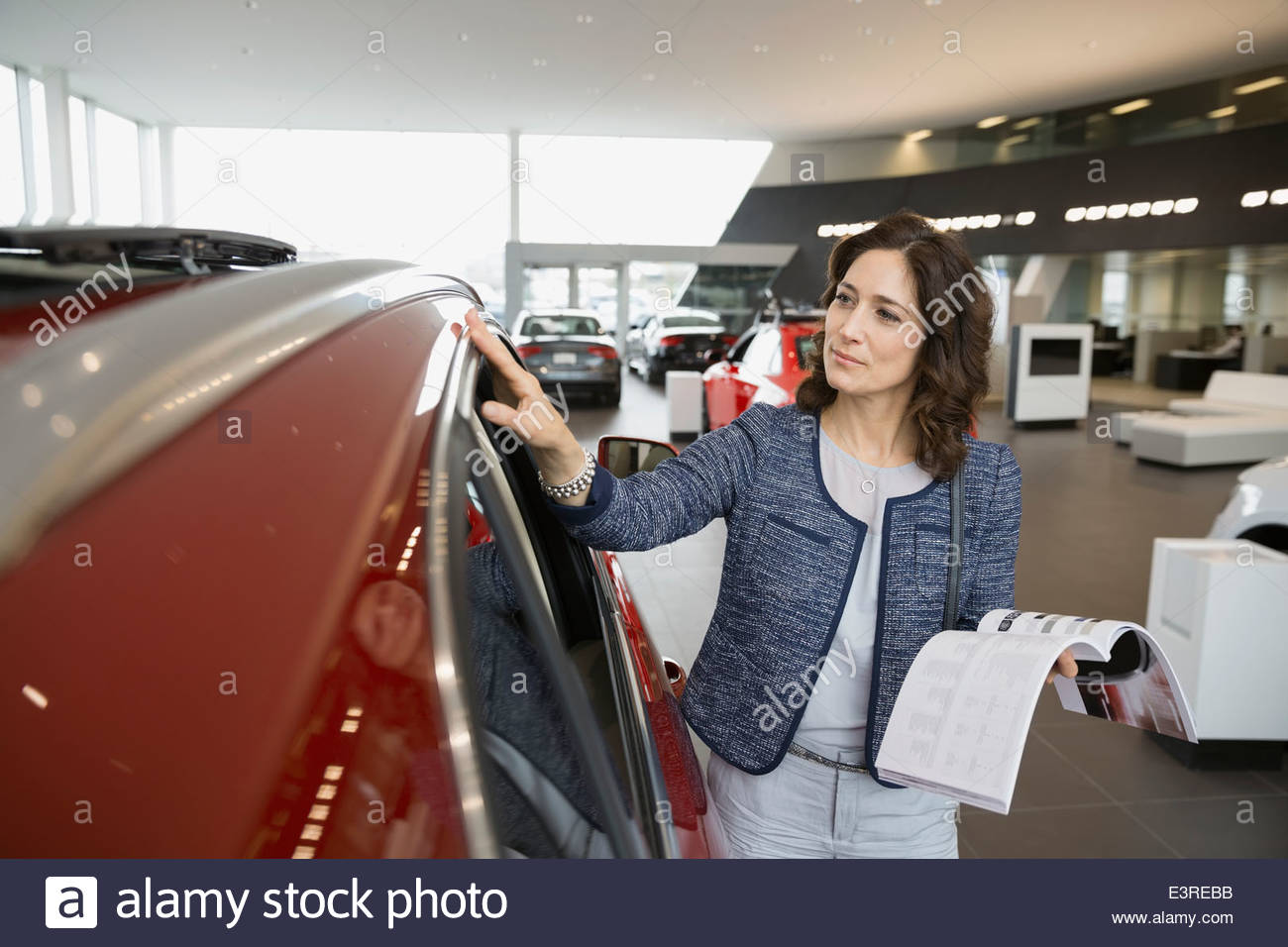 Woman with brochure in car dealership showroom - Stock Image