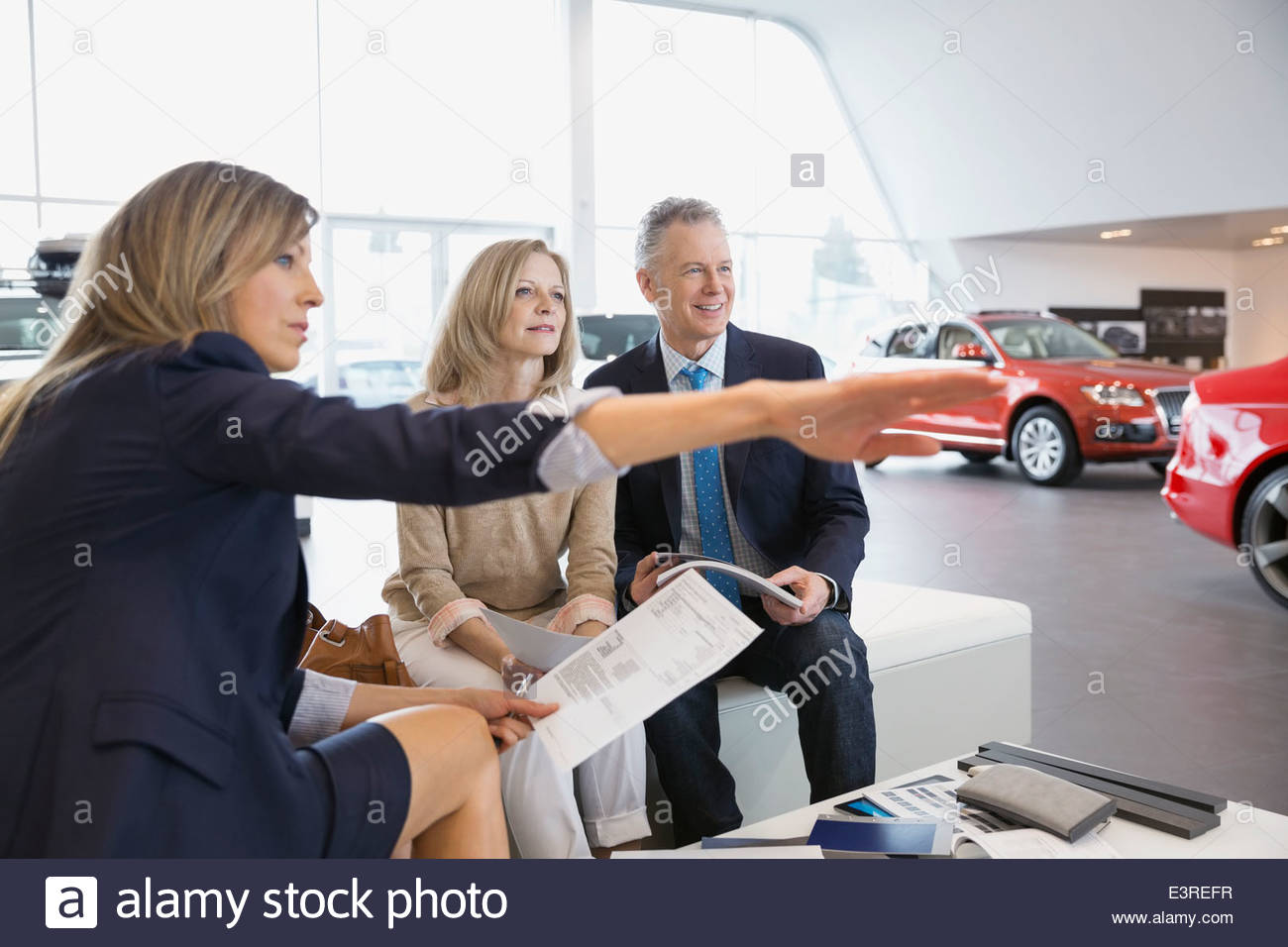 Saleswoman explaining to couple in car dealership showroom - Stock Image