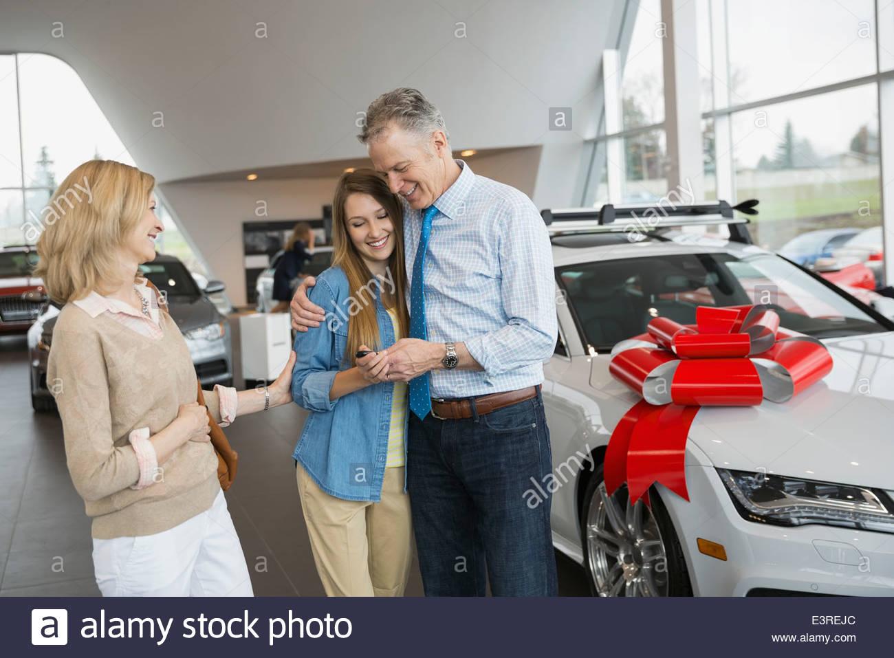 Parents buying daughter car in dealership showroom - Stock Image