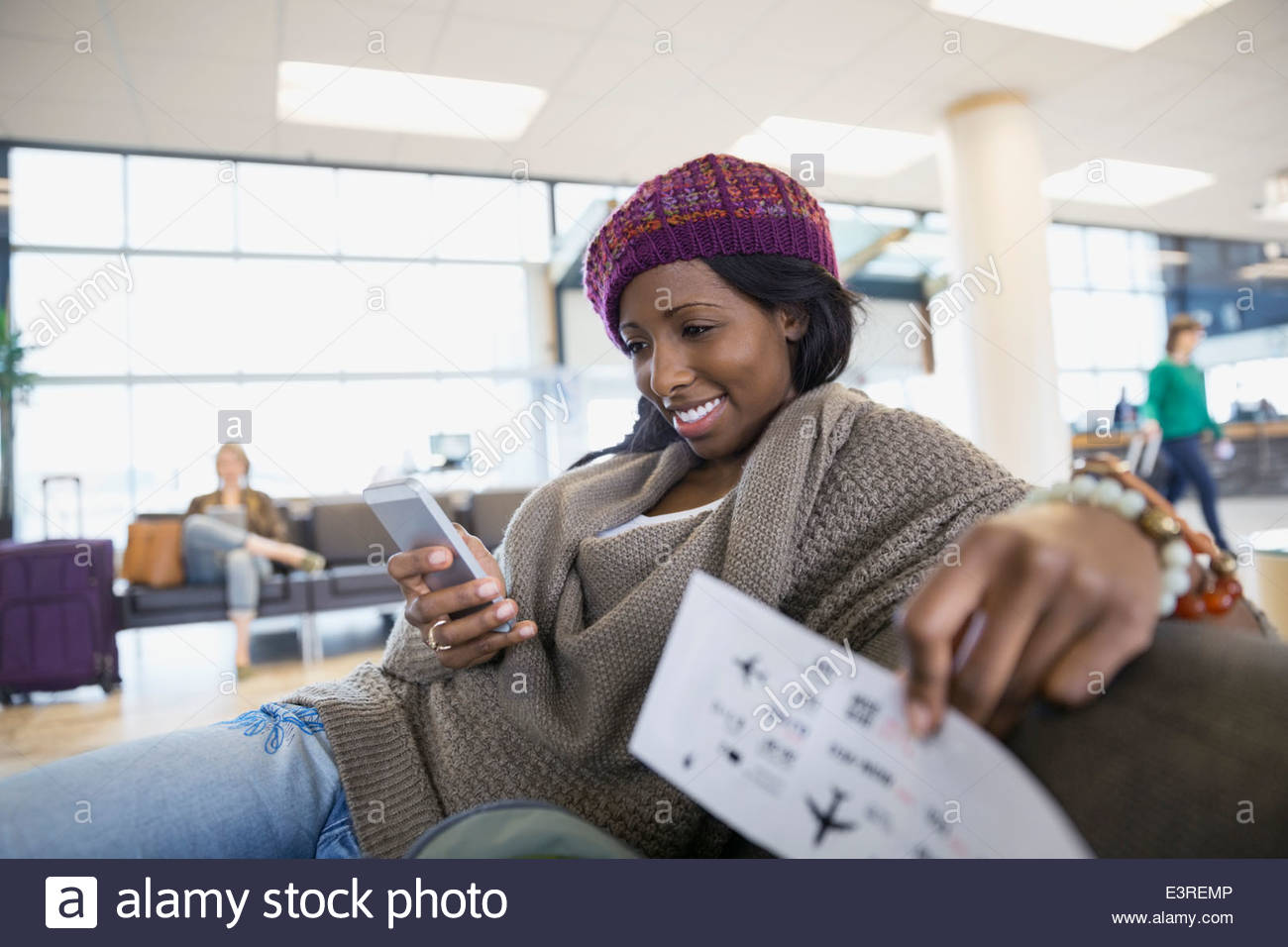 Woman text messaging with cell phone in airport - Stock Image