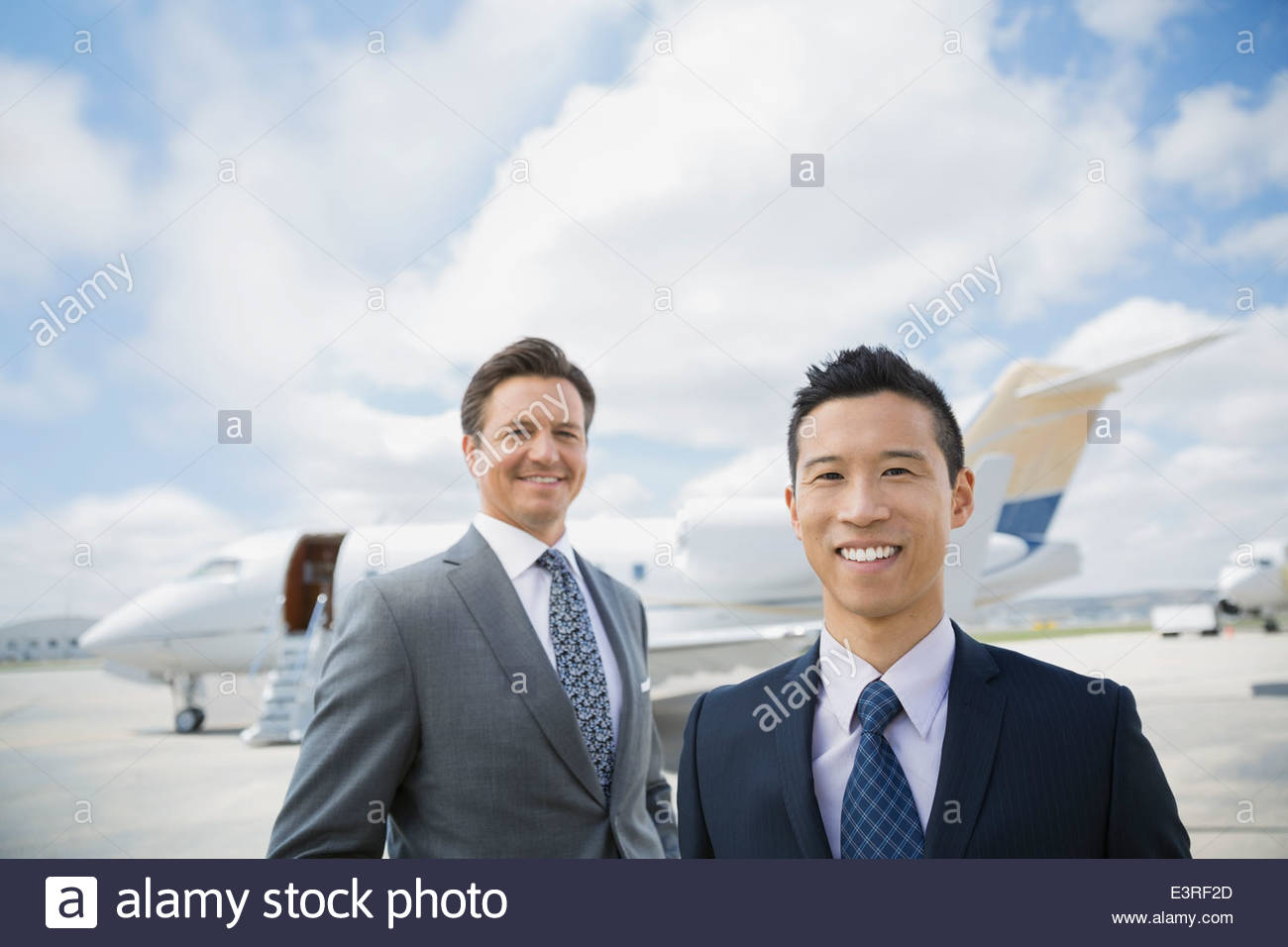 Portrait of businessmen on tarmac with corporate jet - Stock Image