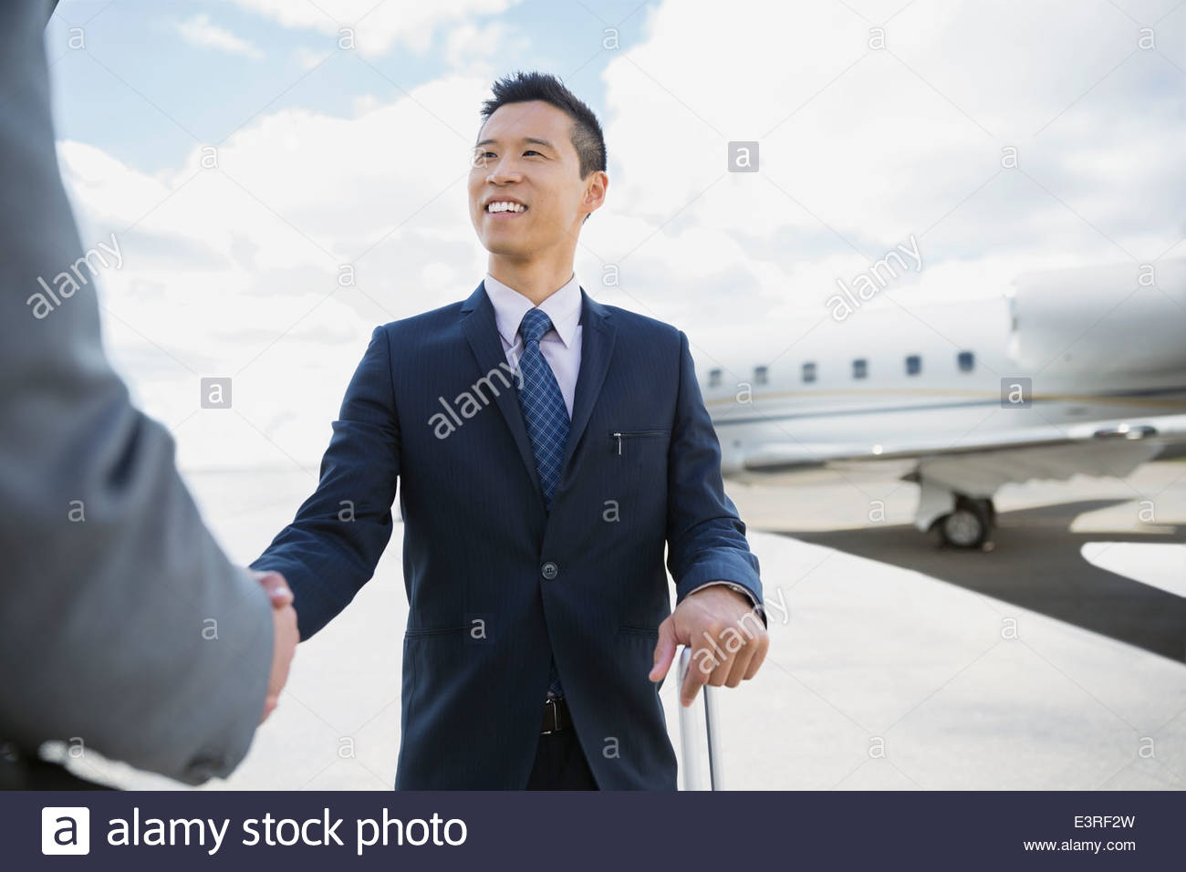 Businessmen handshaking on tarmac with corporate jet - Stock Image