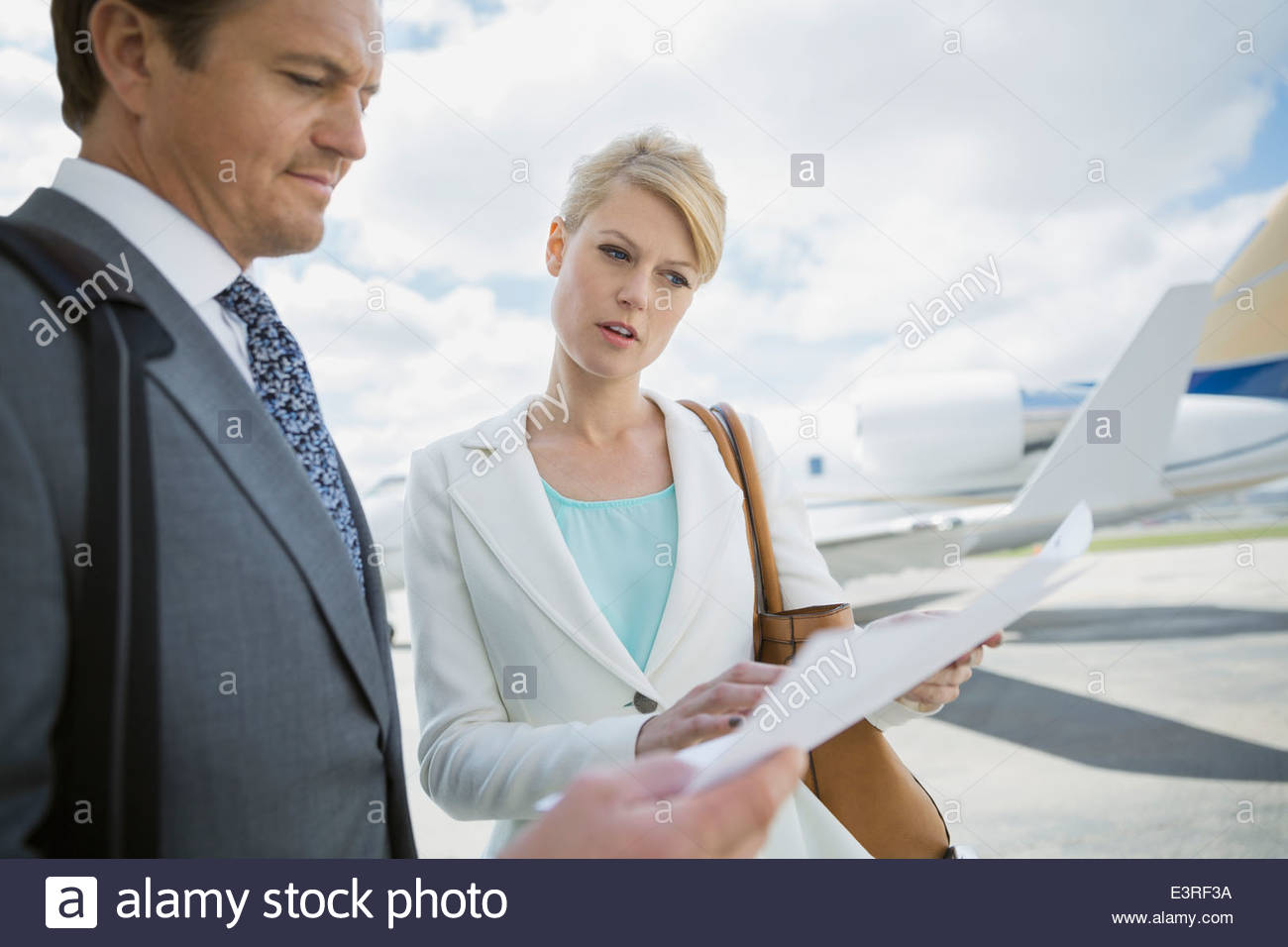 Business people reviewing paperwork on tarmac - Stock Image