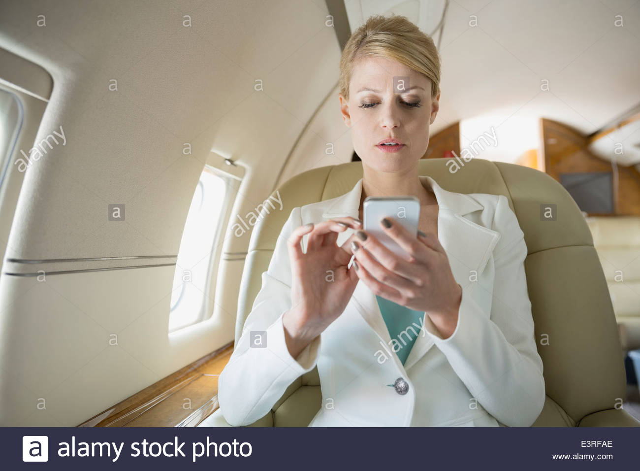 Businesswoman text messaging on corporate jet - Stock Image