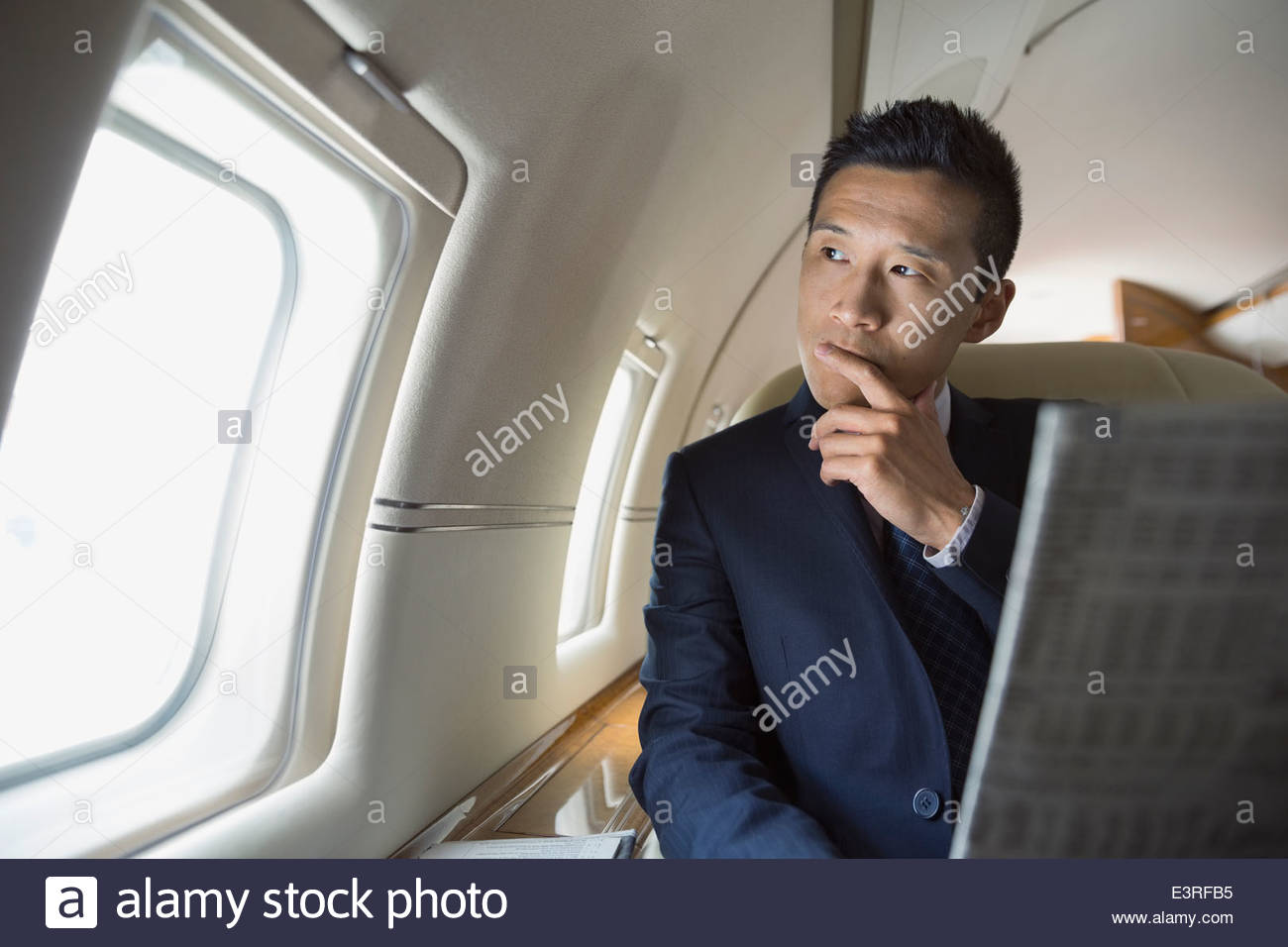 Pensive businessman reading newspaper on corporate jet - Stock Image