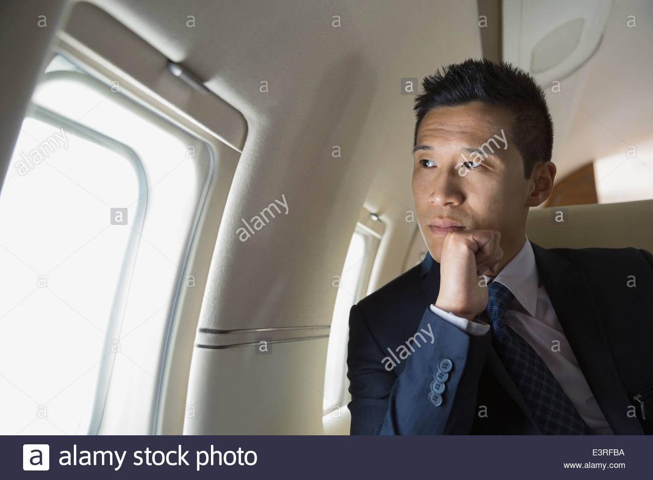 Pensive businessman looking at window of corporate jet - Stock Image