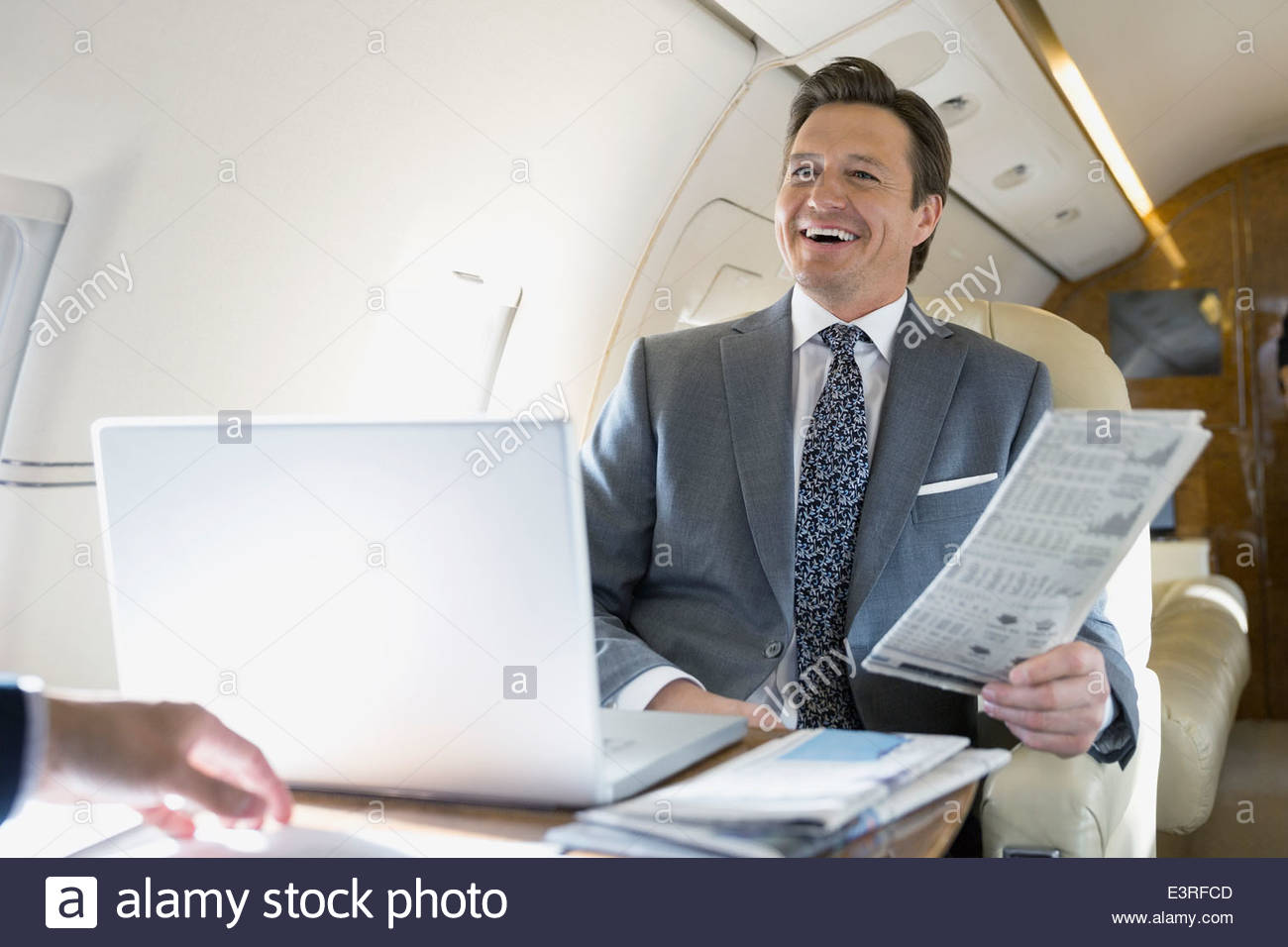 Businessman with newspaper laughing on corporate jet - Stock Image