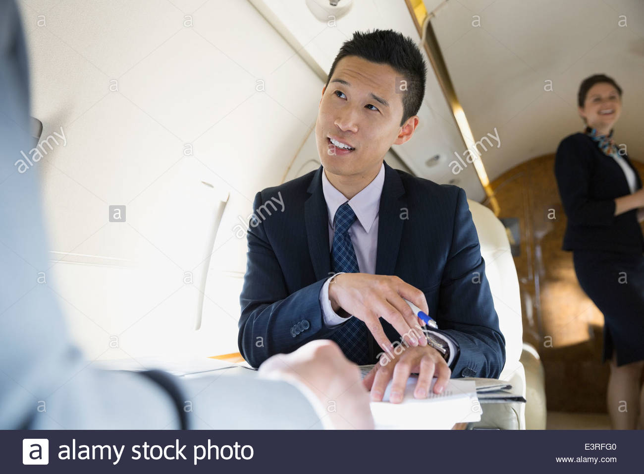 Businessmen talking on corporate jet - Stock Image
