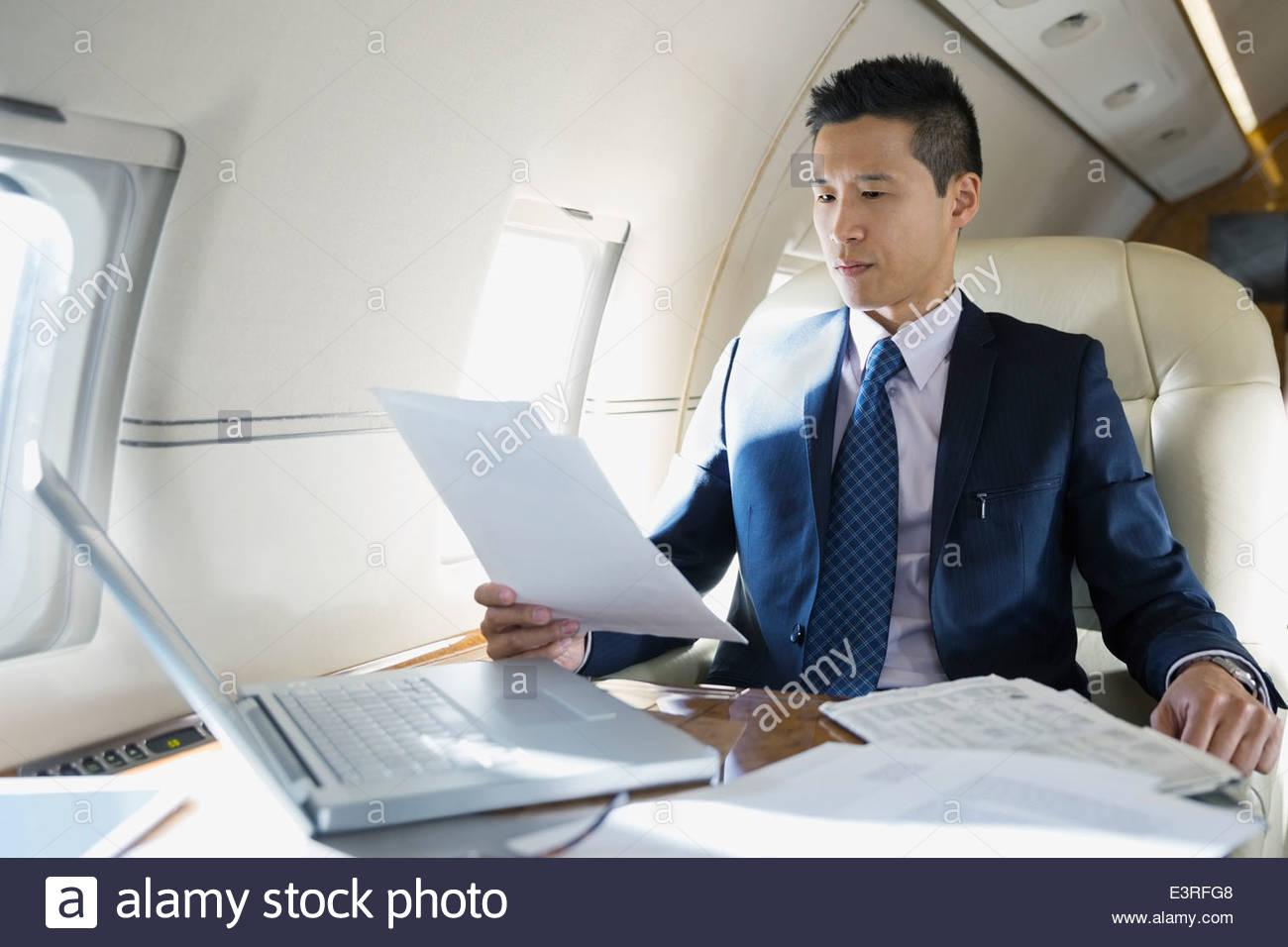 Businessman working on corporate jet - Stock Image