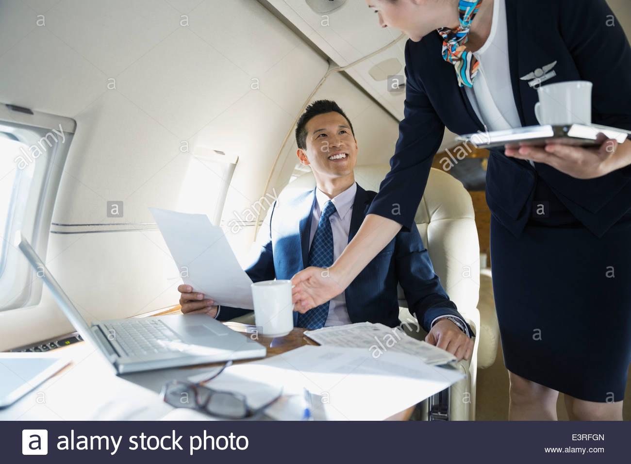 Flight attendant serving businessman on corporate jet - Stock Image