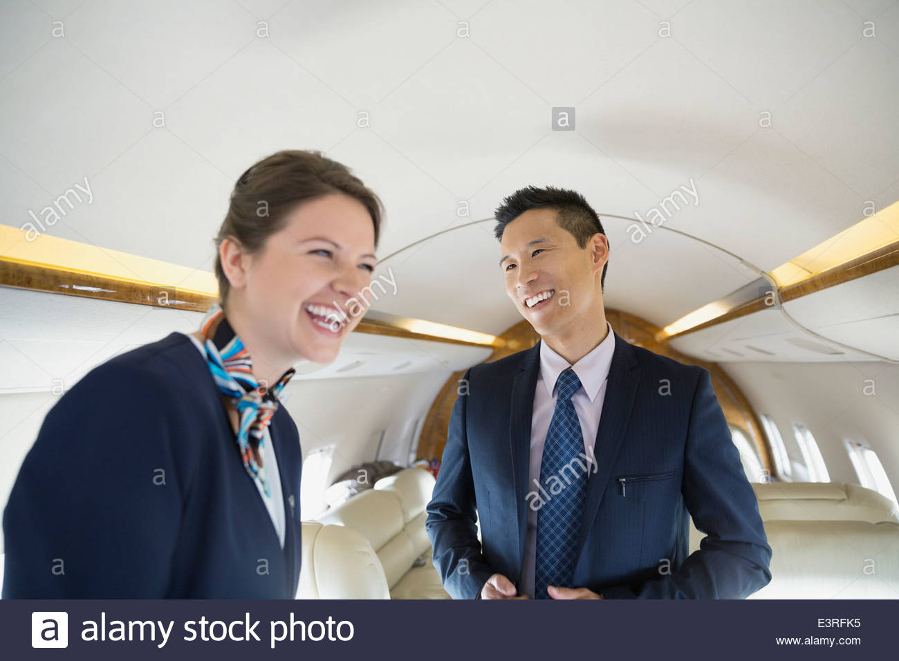 Businessman and flight attendant laughing on corporate jet - Stock Image
