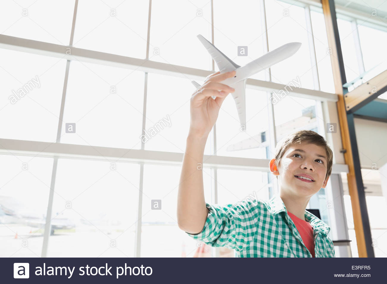 Boy playing with toy airplane in airport - Stock Image