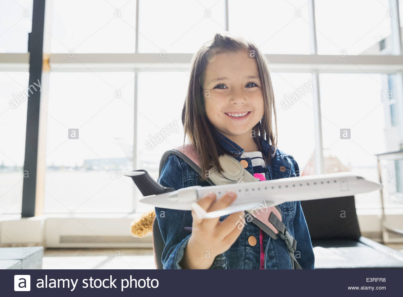 Girl playing with toy airplane in airport - Stock Image