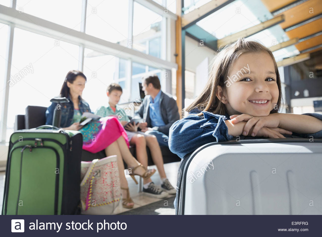 Portrait of smiling girl waiting in airport - Stock Image