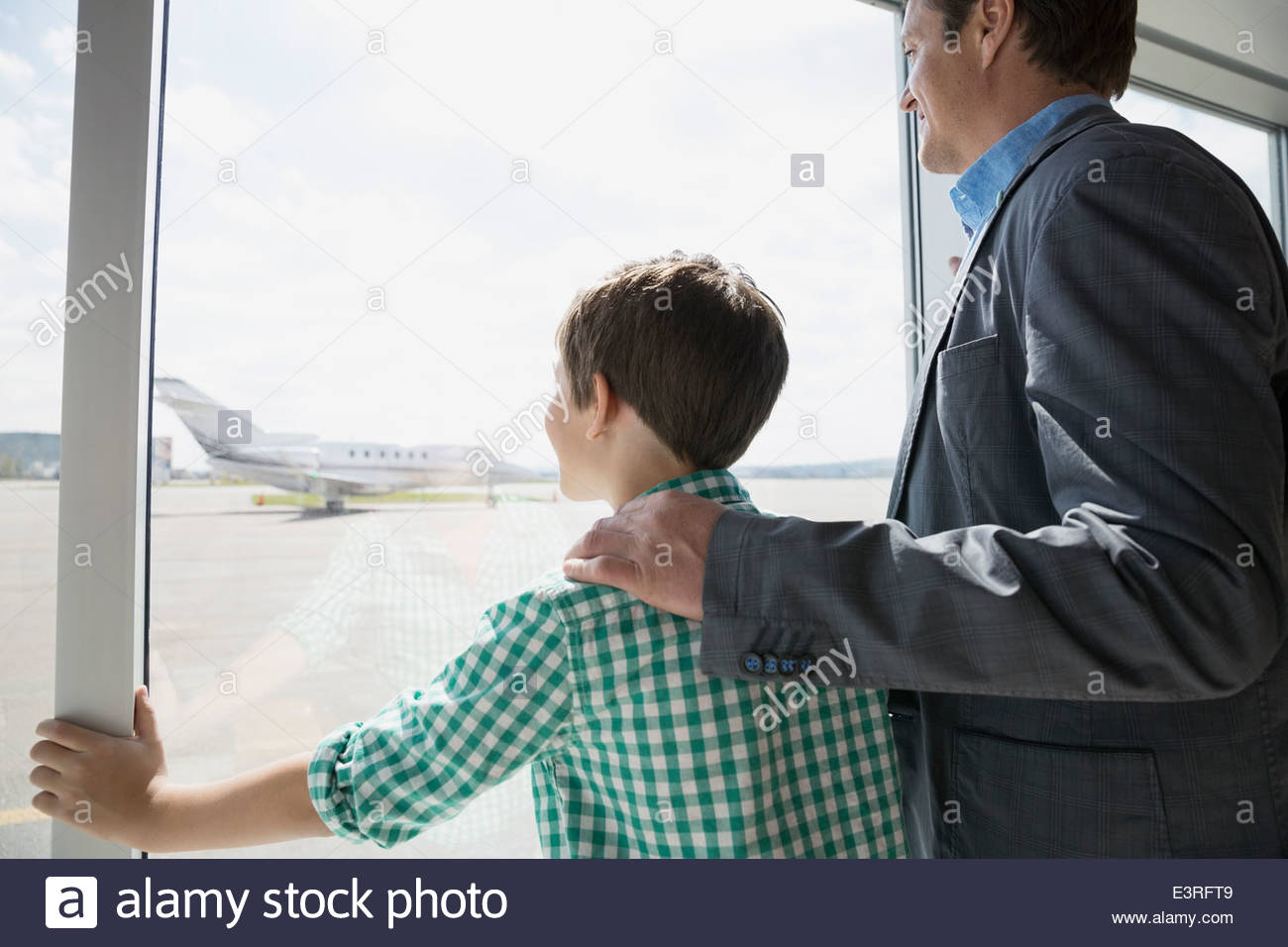 Father and son at sunny airport window - Stock Image
