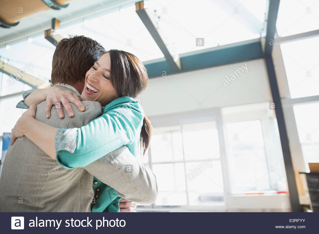 Enthusiastic couple hugging in airport - Stock Image
