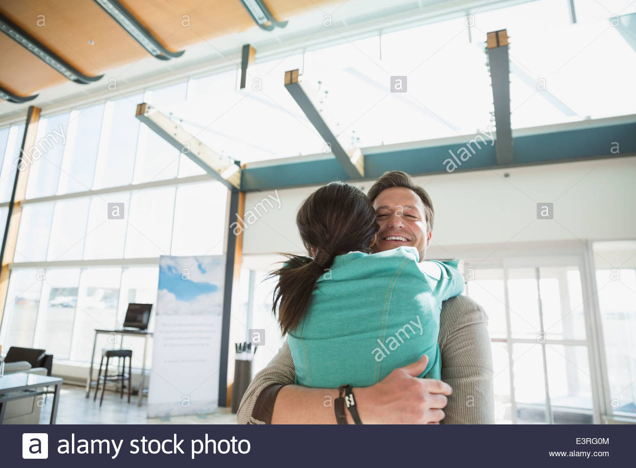 Smiling couple hugging in airport - Stock Image