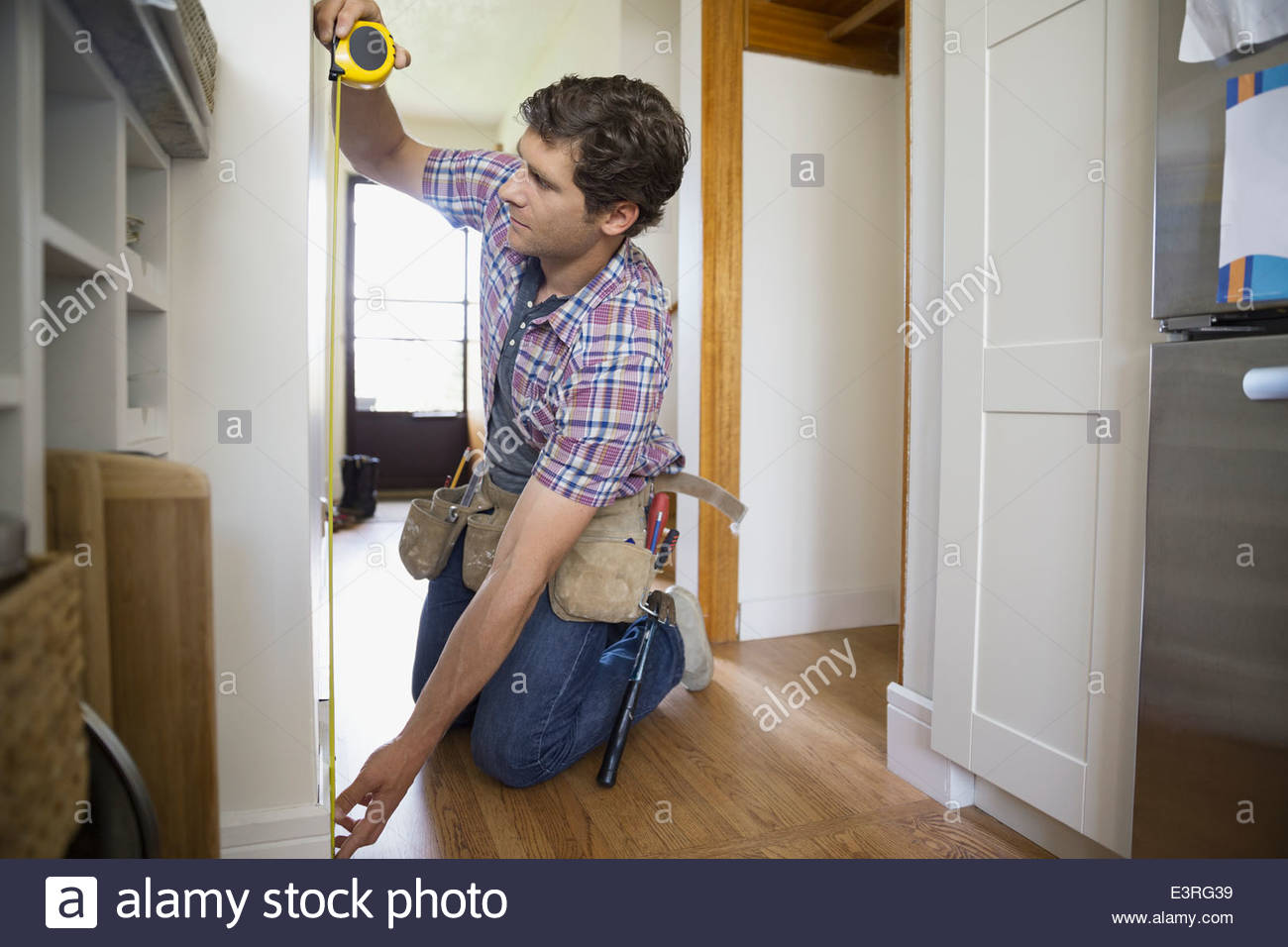 Man measuring wall with tape measure - Stock Image