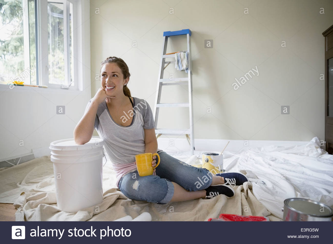 Smiling woman drinking coffee on paint drop cloth - Stock Image