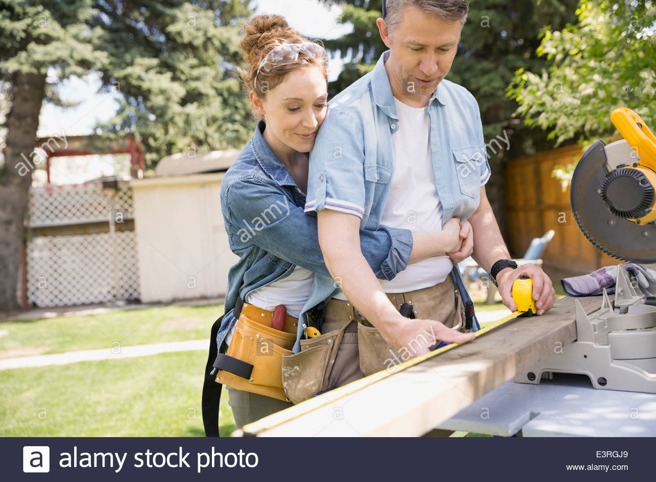 Man measuring wood plank at table saw - Stock Image