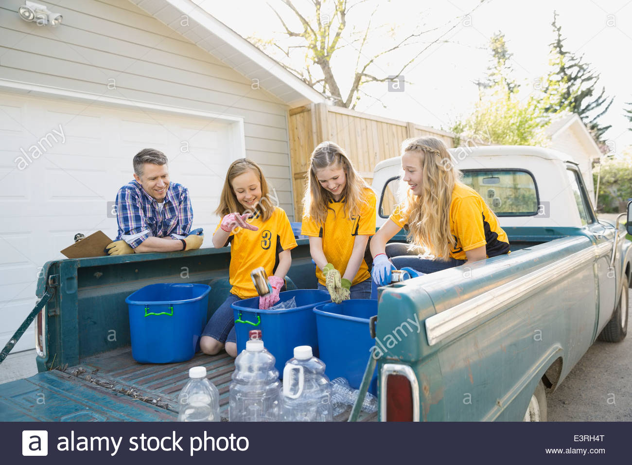 Girls in uniforms sorting recycling in truck bed - Stock Image