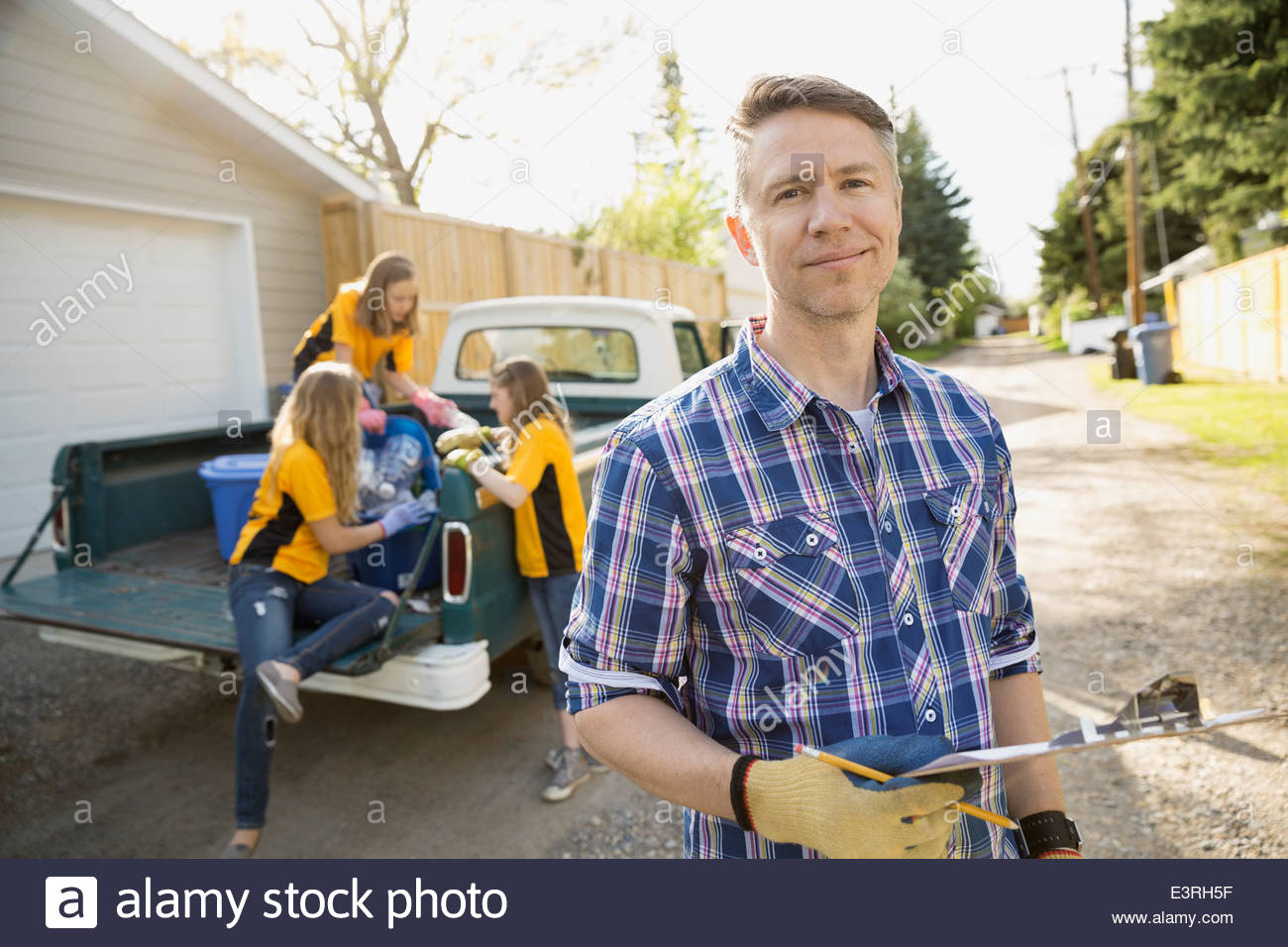 Father and daughters recycling - Stock Image