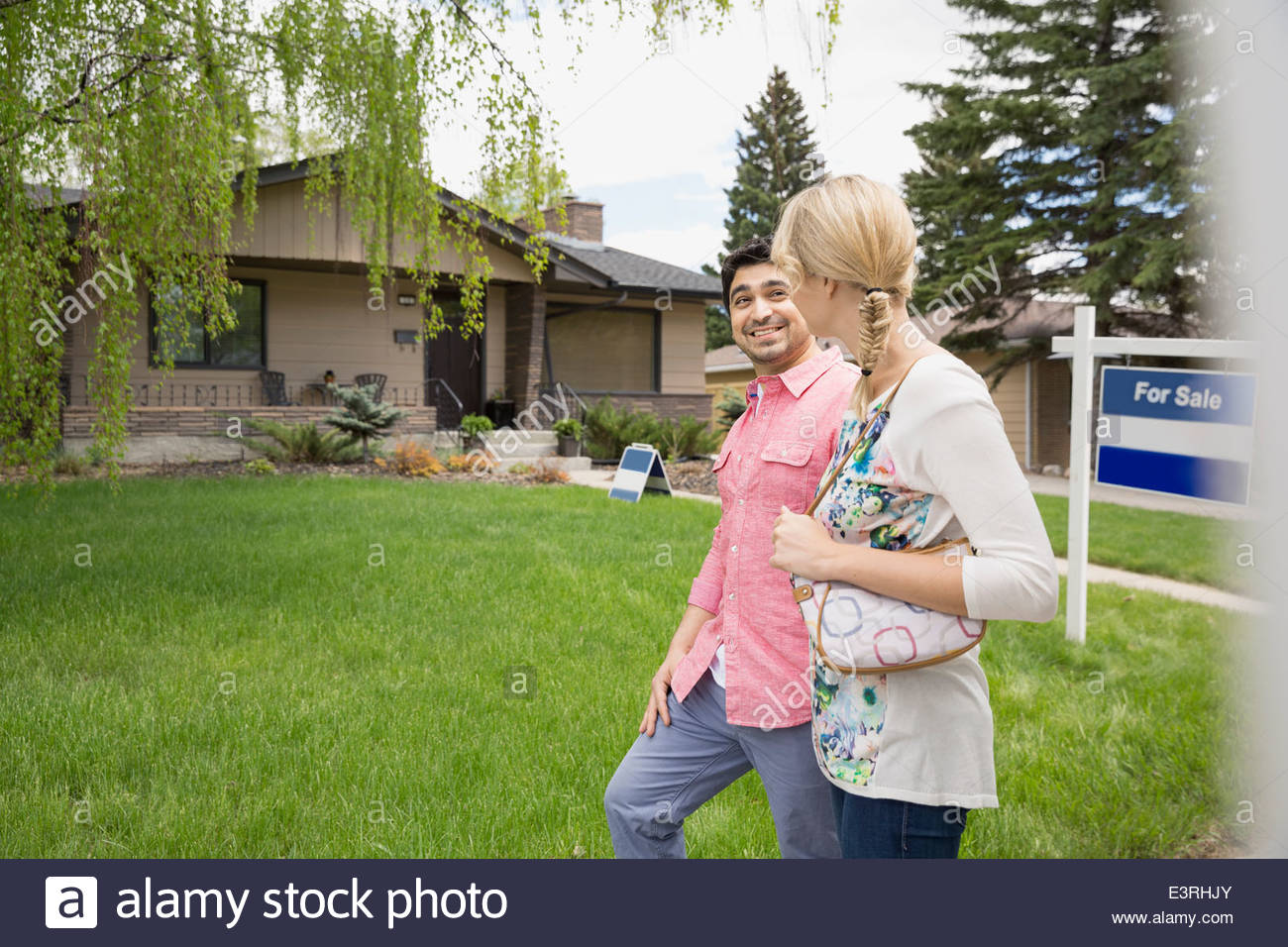Couple walking outside house with For Sale sign - Stock Image