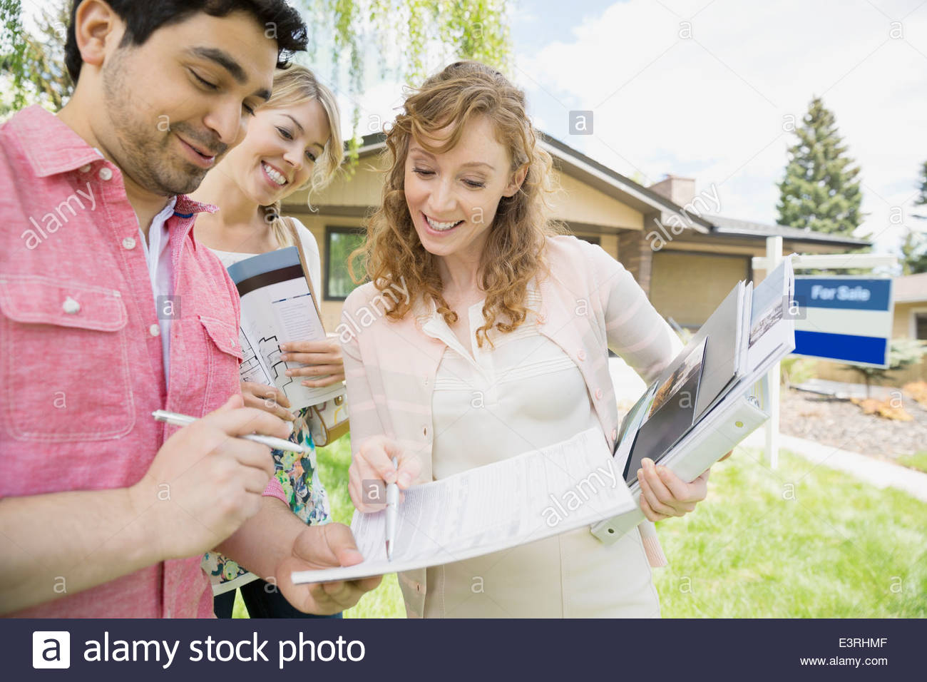 Couple signing paperwork with realtor outside house - Stock Image