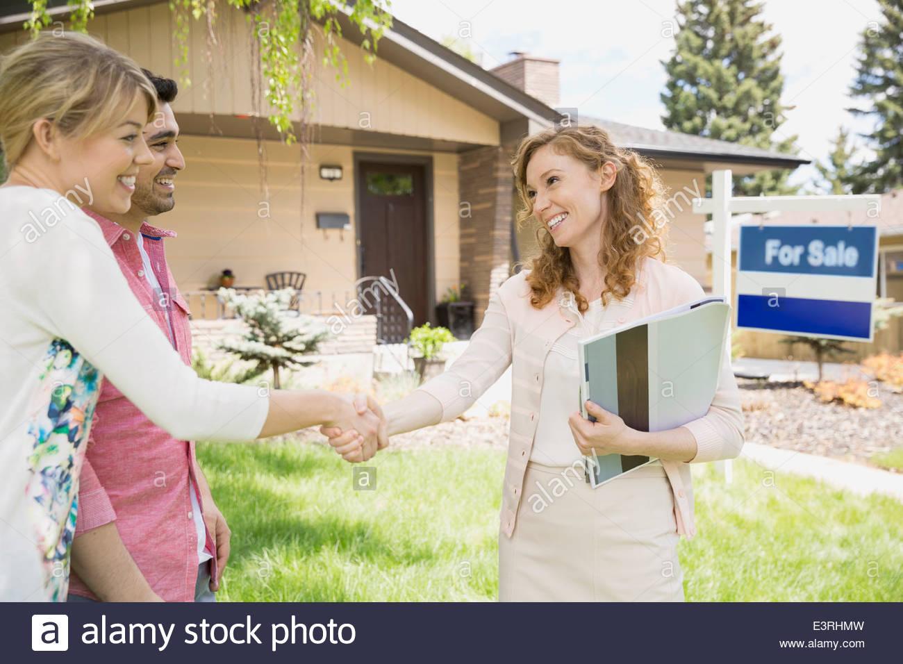 Realtor and couple handshaking outside house - Stock Image