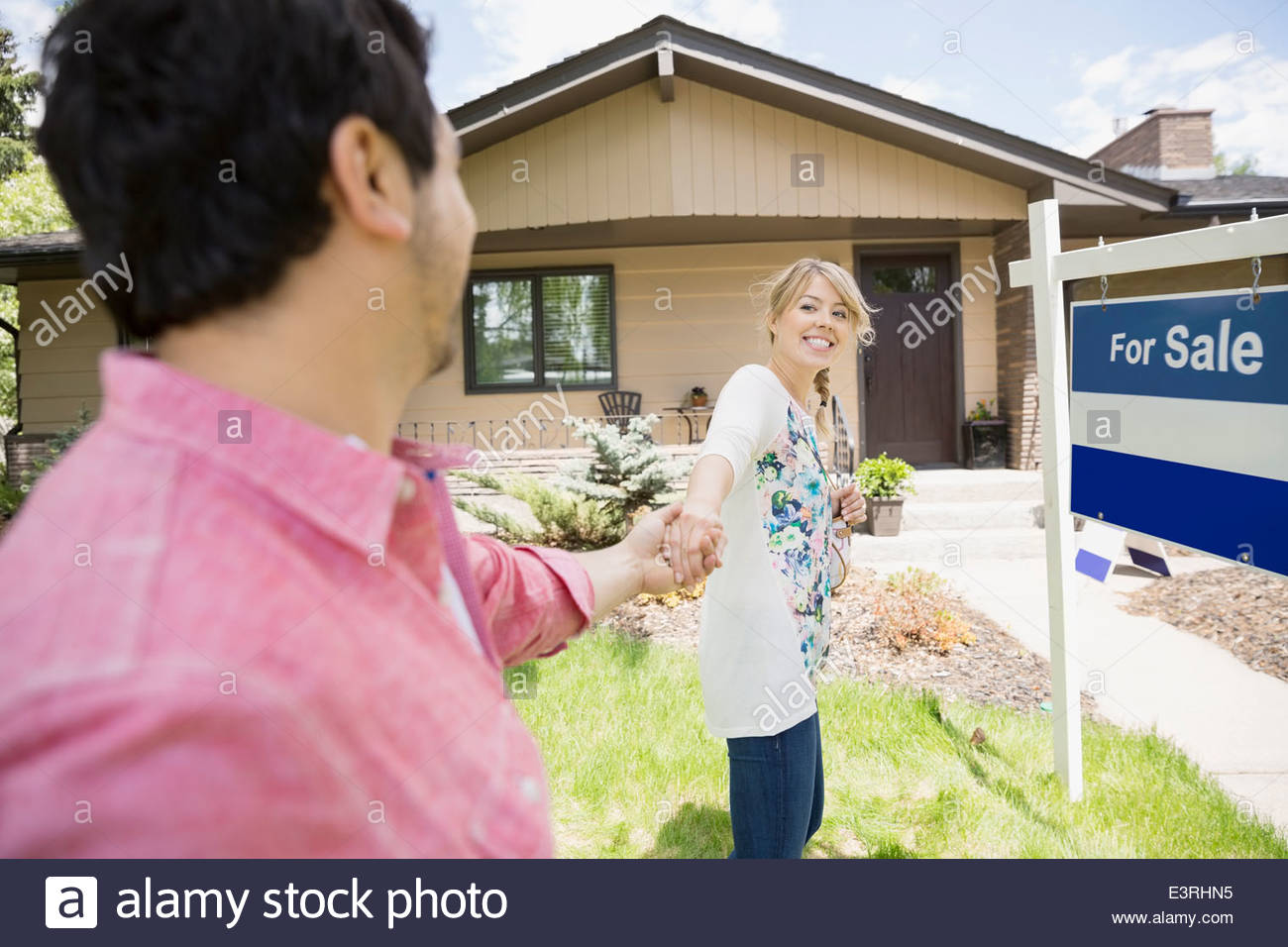 Couple holding hands outside house for sale - Stock Image