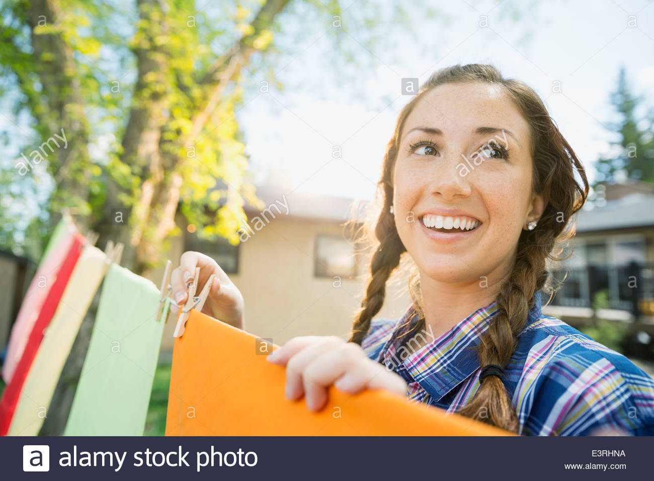 Smiling woman with braids hanging laundry on clothesline - Stock Image