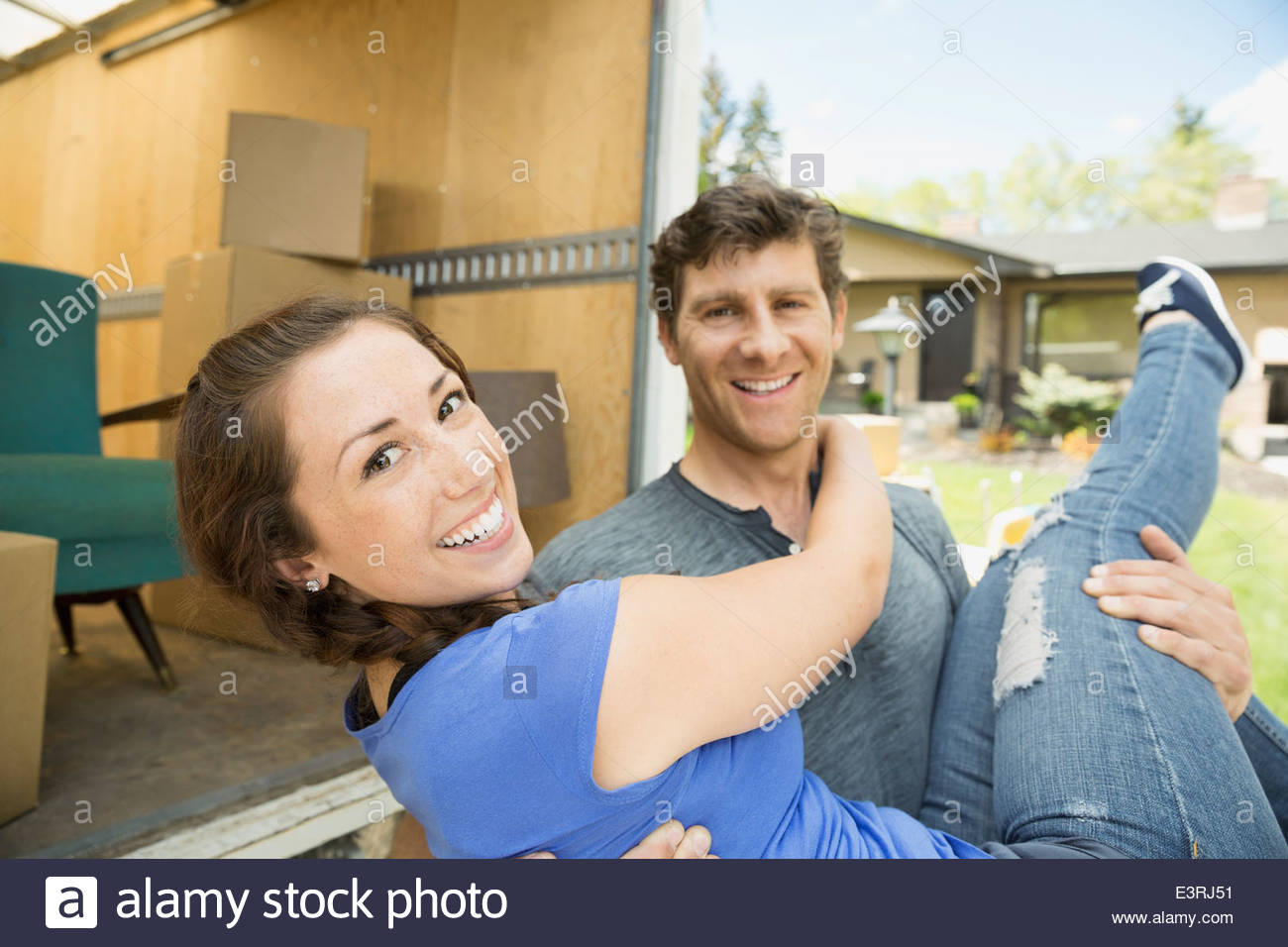 Portrait of man carrying woman outside moving van - Stock Image