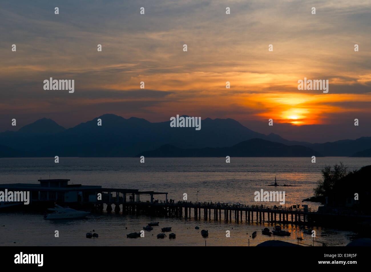 sunset over the Lamma Island ferry pier, Yung Shue Wan, Lamma Island, Hong Kong, China Stock Photo