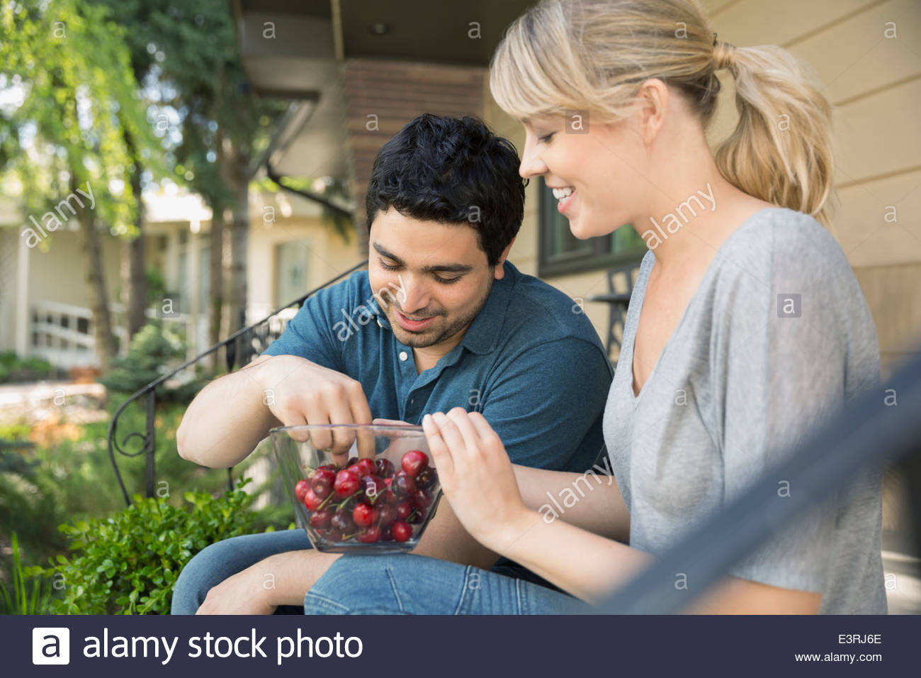 Couple eating cherries on front stoop - Stock Image