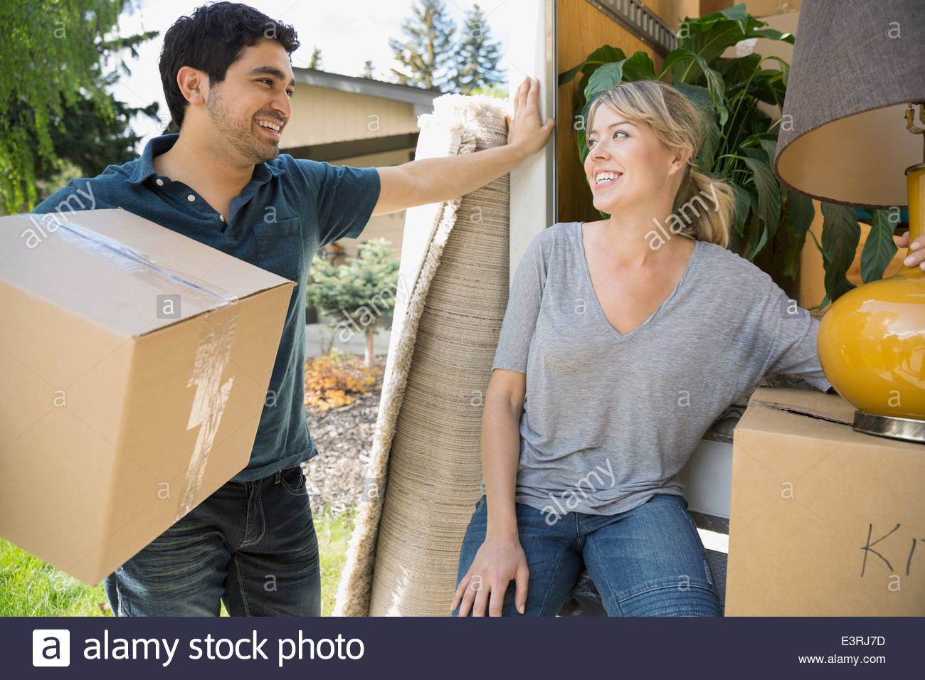 Couple unloading belongings from moving van Stock Photo