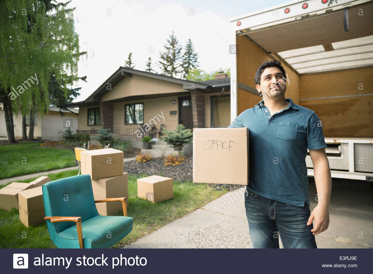 Man holding box outside moving van in driveway - Stock Image