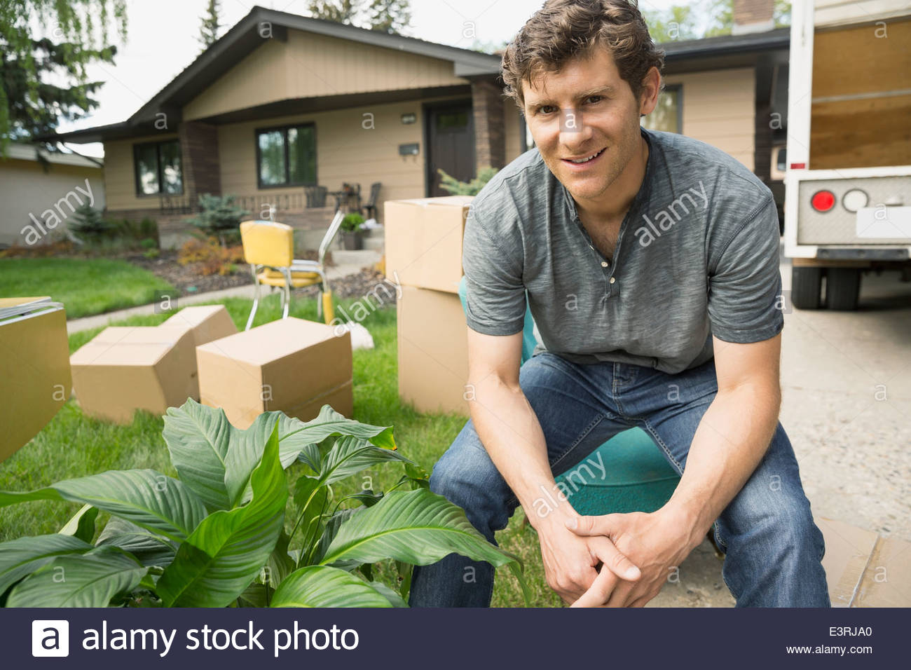 Portrait of confident man sitting outside moving van - Stock Image