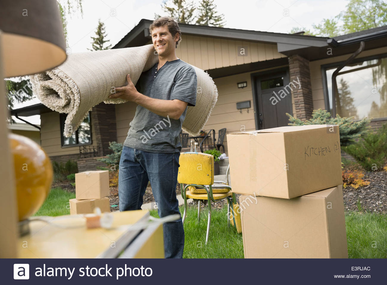 Man carrying rug among belongings in front yard - Stock Image