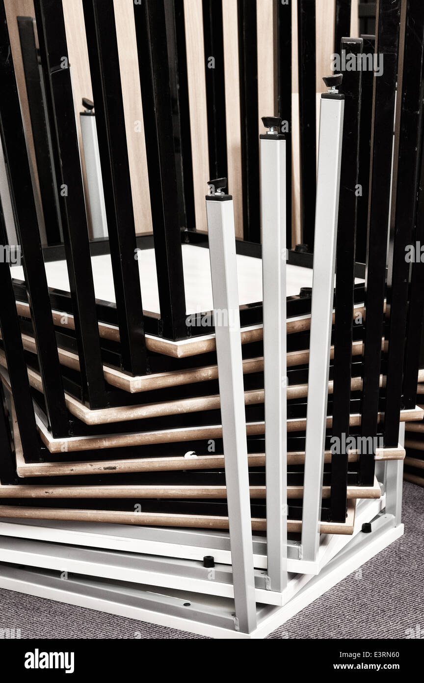 Inverted upside down stacked metal tables deck legs making a pattern of bars spiraling upwards at corners - Stock Image