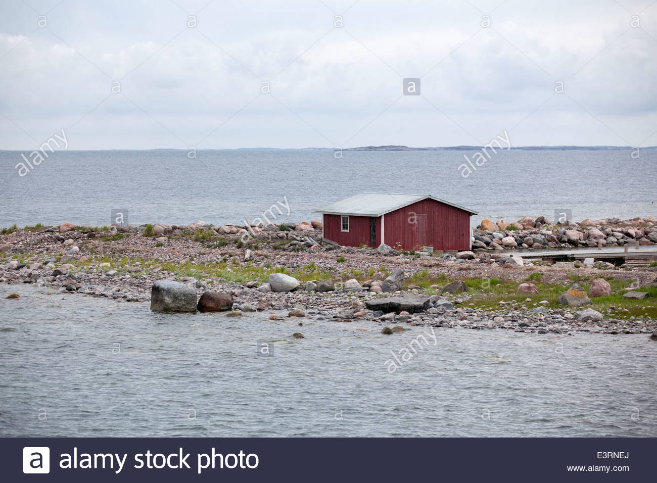Red shed on the shore of Jurmo island in outer archipelago of Finland - Stock Image