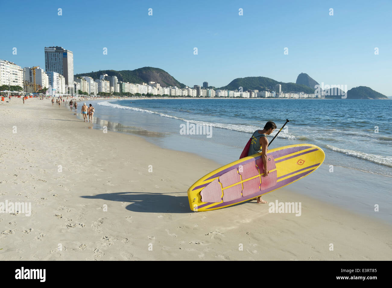 RIO DE JANEIRO, BRAZIL - JANUARY 31, 2014: Brazilian man carries a stand up paddle longboard surfboard into the - Stock Image
