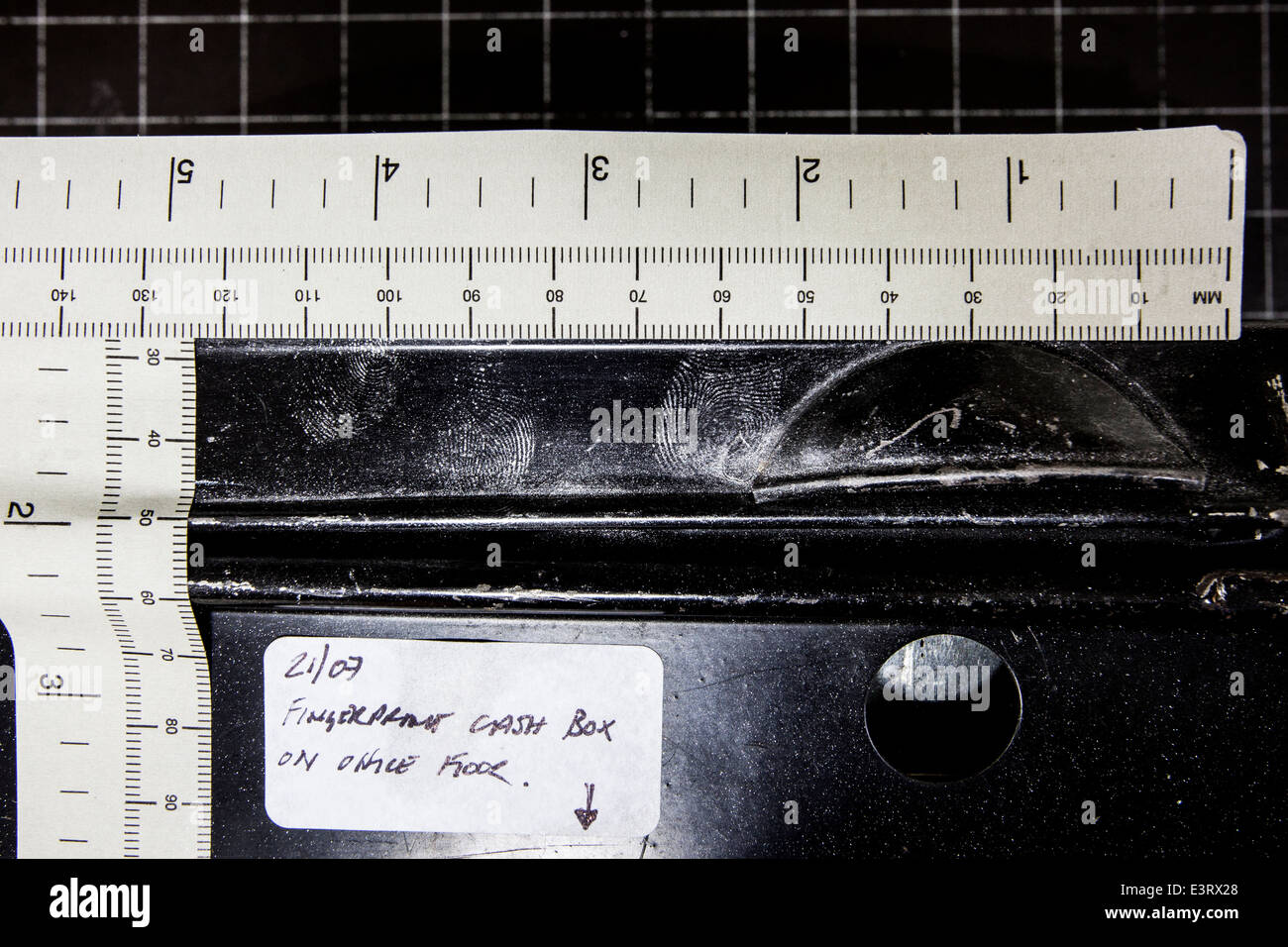 Crime scene examination of a cash tin with aluminium powder showing enhanced fingerprints in the silver power - Stock Image