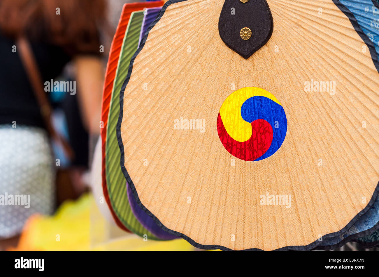 A fan painted with a traditional Korean symbol hangs outside a vendor in the Insadong district of Seoul, South Korea. - Stock Image