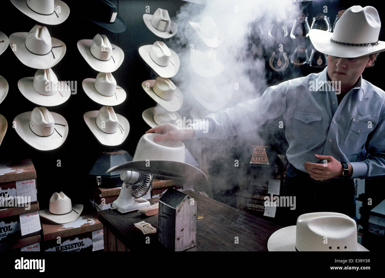 c9c661bf596 A professional hatter uses steam to custom shape the crown and brim of a  white straw