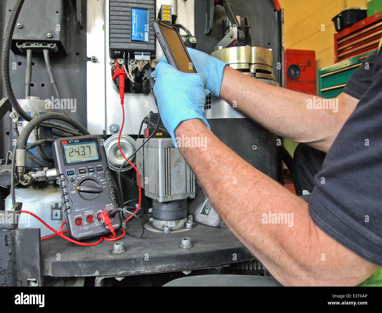 Technician browsing Internet on Mobile phone while carrying out repairs to Truck - Stock Image