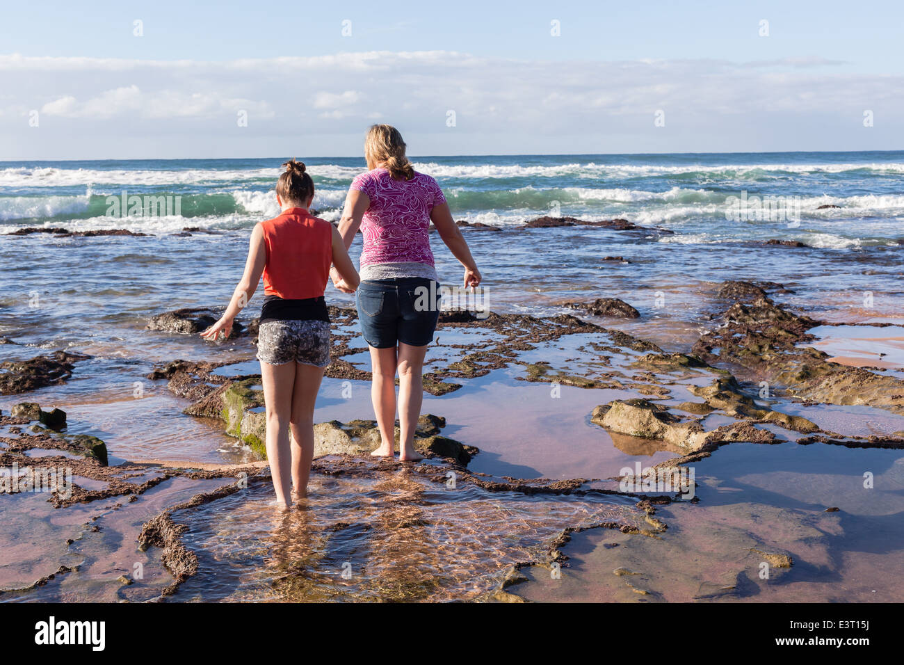 Mother daughter walking exploring beach ocean shallow exposed reefs rear photo. - Stock Image