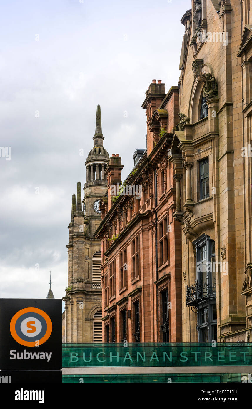 Buchanan Street, Glasgow with the subway access sign, and the spire of the local church, Scotland, UK - Stock Image