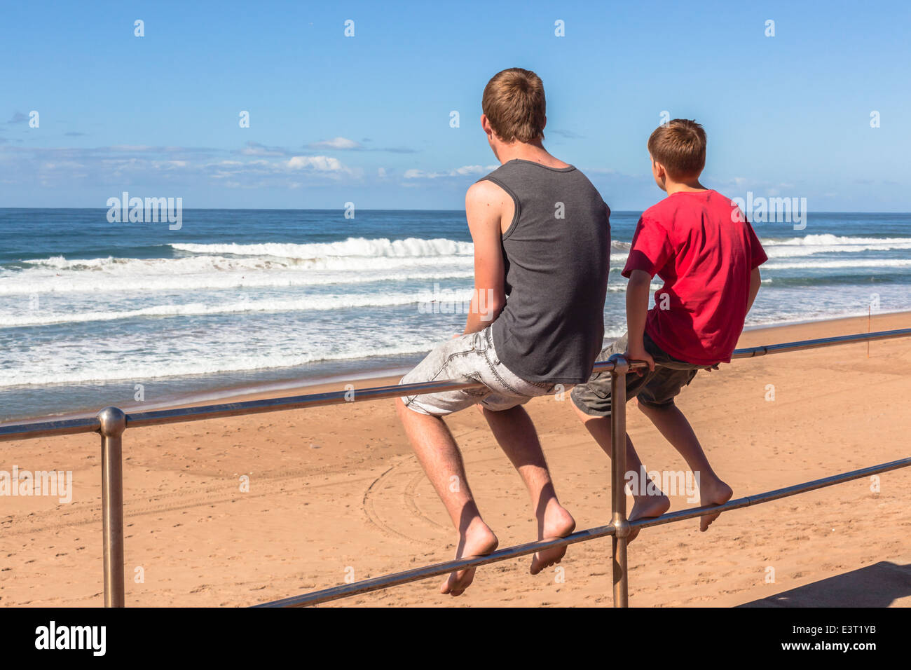 teenager boys sitting on railing relaxing at the beach watching