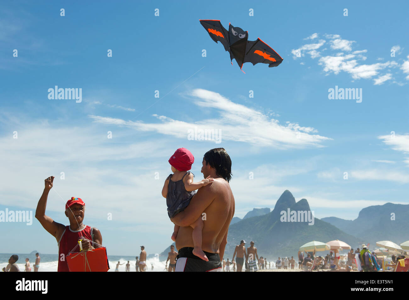 RIO DE JANEIRO, BRAZIL - MARCH 10, 2013: A beach vendor selling kits displays his merchandise for a father and child - Stock Image